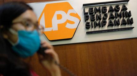 Karyawan beraktivitas didekat logo Lembaga Penjamin Simpanan (LPS) di Jakarta, Jum'at, 10 Juli...