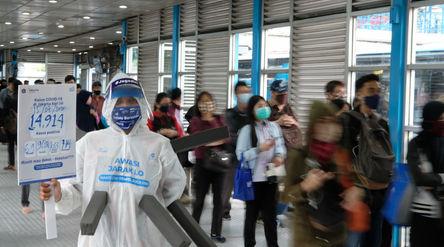 Maskot 'Manusia Covid' dari anggota komunitas pecinta Transjakarta mengenakan hazmat den...