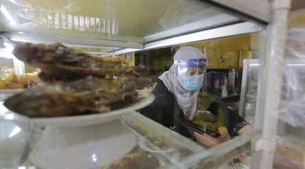 Penjual menggunakan masker dan faceshield saat melayani pelanggan di Warung Tegal (Warteg) Ellya, Ci...