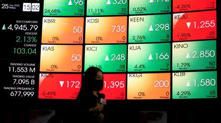 Awak media melakukan peliputan dengan latar belakang layar pergerakan Indeks Harga Saham Gabungan (I...