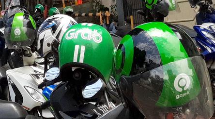 Atribut helm pengemudi ojek daring GrabBike dan Gojek tampak di atas armada yang terparkir di kawasa...