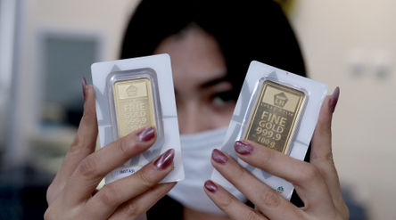 Karyawati menunjukkan replika emas logam mulia di Butik Emas LM ANTAM, Kebun Sirih, Jakarta, Senin, ...