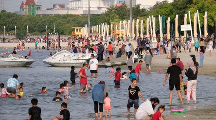 Wisatawan menikmati waktu berlibur di Pantai Lagoon, Taman Impian Jaya Ancol, Jakarta, Kamis, 29 Okt...