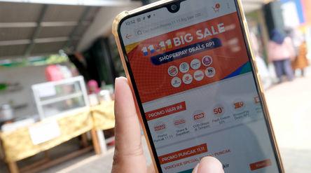 Warga mengakses salah satu platform e-commerce untuk berbelanja secara daring melalui gawai dalam ra...