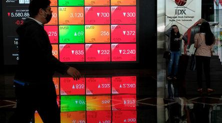 Karyawan beraktivitas dengan latar belakang layar pergerakan Indeks Harga Saham Gabungan (IHSG) di G...