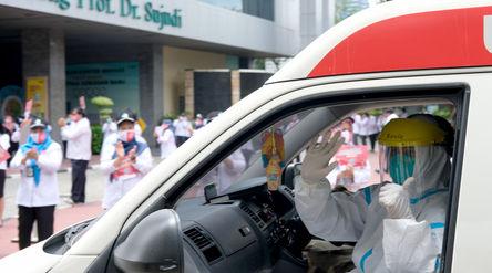 Petugas medis melambaikan tangan kepada jajaran karyawan Kementerian Kesehatan (Kemenkes) yang melak...