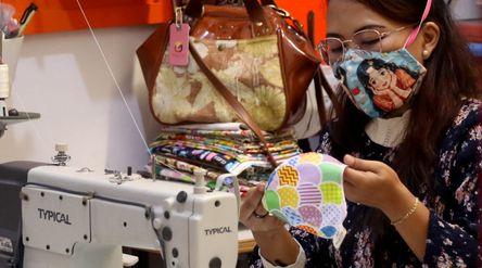 Perajin menyelesaikan produksi masker gambar karakter di industri rumahan Yesya Frita Indonesia, Kot...