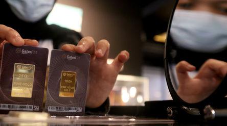 Karyawati menunjukkan emas batangan di gerai emas Pegadaian, Jakarta, Selasa, 15 Desember 2020. Foto...