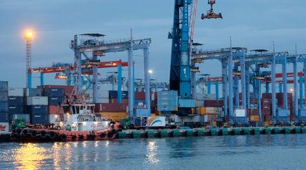 Kapal bersandar didekat crane bongkar muat peti kemas di dermaga Pelabuhan Tanjung Priok, Jakarta, S...