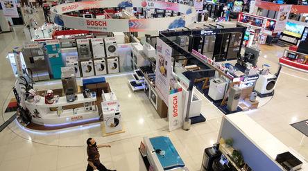 Calon pembeli melintas di antara produk elektronik yang di pajang di Gerai Electronic City, kawasan ...