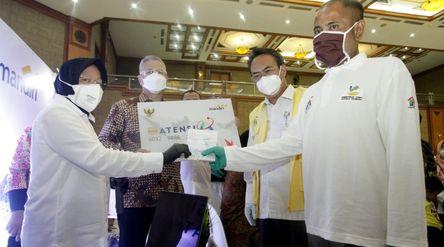 Menteri Sosial (Mensos) Tri Rismaharini (kiri) menyerahkan dokumen dan mock up kartu peserta program...