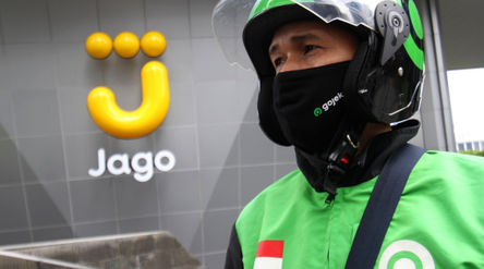 Mitra Driver Gojekmenunggu customer di dekat logo Bank Jago di kawasan Mega Kuningan, Jakarta, Sela...