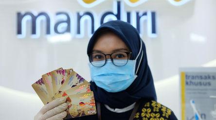 Karyawati menunjukkan kartu debit ATM dengan chip di kantor cabang Bank Mandiri Edu-Branch, Pondok I...