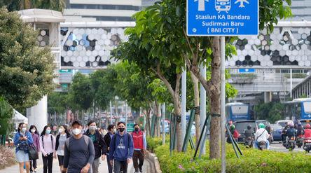 Pekerja melintas pada jam pulang kerja di kawasan Jalan Jenderal Sudirman, Jakarta, Senin, 22 Februa...