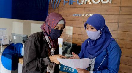 Karyawan melayani nasabah di salah satu kantor cabang PT Federal International Finance Group (FIFGRO...