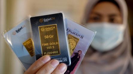 Karyawati menunjukkan emas batangan di gerai Galeri 24 Pegadaian, Jakarta, Senin, 1 Maret 2021. Foto...