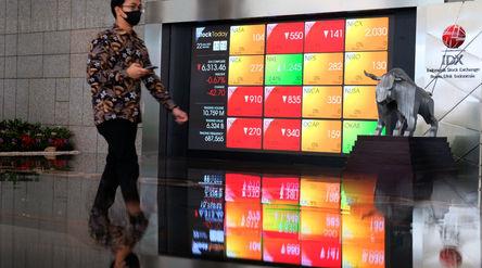 Karyawan melintas dengam latar pergerkan indeks harga saham gabungan (IHSG) di gedung Bursa Efek Ind...