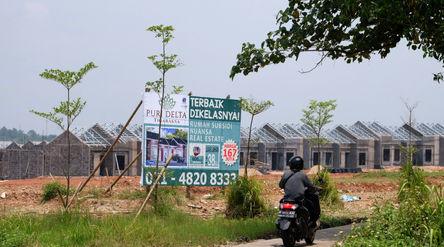 Warga melintas di dekat proyek pembangunan rumah subsidi di kawasan Tigaraksa, Tangerang, Senin, 28 ...