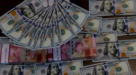 Karyawati menunjukkan mata uang Dolar Amerika dan Rupiah di salah satu teller bank, di Jakarta, Rabu...