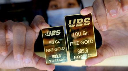 Karyawati menunjukkan emas batangan di gerai Galery 24, Pegadaian, Jakarta, Senin, 5 April 2021. Fot...