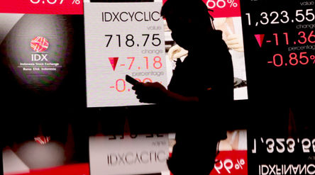 Awak media beraktivitas dengan latar pergerakan indeks harga saham gabungan (IHSG) di Gedung Bursa E...