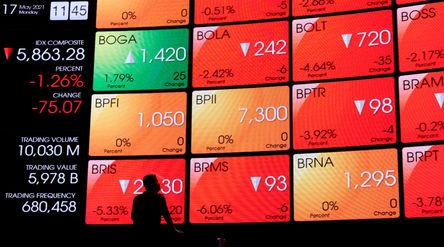 Karyawan beraktivitas dengan latar layar pergerakan indeks harga saham gabungan (IHSG) di gedung Bur...