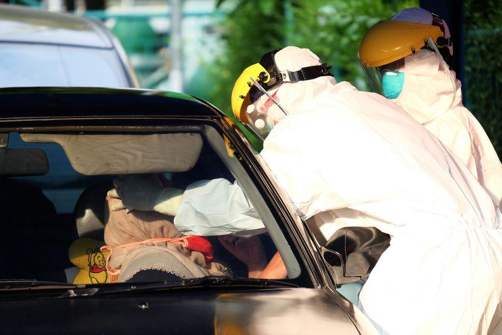 Petugas medis mengambil sampel spesimen saat swab test secara drive thru di halaman Laboratorium Kesehataan Daerah (LABKESDA) Kota Tangerang, Banten 28 April 2020 lalu/ Foto: Ismail Pohan/TrenAsia\n