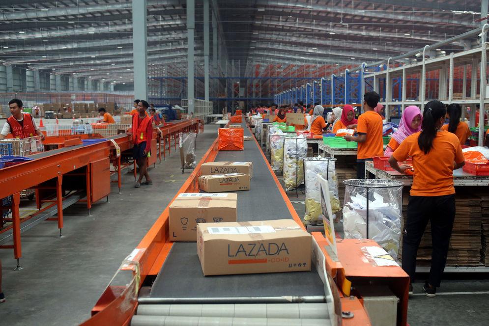 Pekerja menyiapkan barang pesanan untuk dikirimkan kepada pembeli di gudang toko daring Lazada di Cimanggis, Depok, Jawa Barat, Selasa (23/5). Untuk mengimbangi perkembangan. Foto: Ismail Pohan/TrenAsia\n