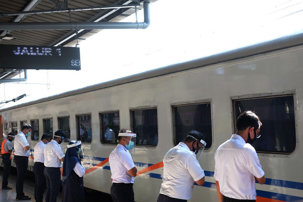 Sejumlah karyawan PT.KAI memberikan salam menghadap rangkaian kereta api jarak jauh KA Serayu relasi Pasar Senen- Purwokerto saat diberangkatkan dari Stasiun Pasar Senen, Jakarta, Jum'at 12 Juni 2020. PT Kereta Api Indonesia (Persero) kembali mengoperasikan kereta api (KA) jarak jauh dan KA lokal reguler secara bertahap mulai hari ini. Pengoperasian kembali KA Reguler ini akan tetap diikuti dengan protokol pencegahan penyebaran Covid-19 yang diterapkan pada Masa Adaptasi Kebiasaan Baru. Foto: Ismail Pohan/TrenAsia\n