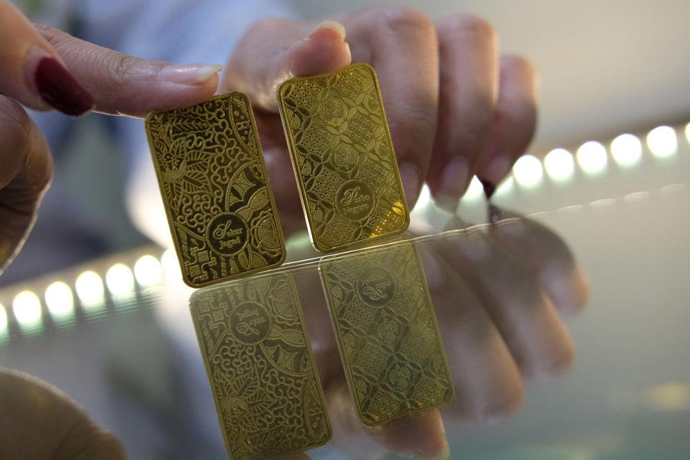 Karyawan menunjukkan logam mulia di Butik Emas Antam, Jakarta, Kamis, 23 Juli 2020. Harga emas batangan PT Aneka Tambang Tbk. (Antam) pada hari ini, Kamis 23 Juli 2020 dipatok lebih rendah untuk ukuran 1 gram dibanderol Rp977.000, sedangkan pada posisi kemarin, Rabu 22 Juli 2020 sempat menyentuh level baru Rp982.000 untuk ukuran 1 gram, yang merupakan level tertinggi sepanjang sejarah. PT Aneka Tambang Tbk. melansir penjualan emas di tingkat ritel tetap menggeliat kendati harga emas menyentuh rekor baru. Penjualan secara daring atau online diakui meningkat signifikan dalam tiga bulan terakhir. Foto: Ismail Pohan/TrenAsia\n
