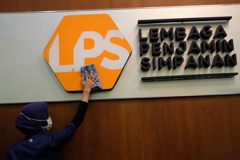 Karyawan membersihkan logo Lembaga Penjamin Simpanan (LPS) di Jakarta, Jum'at, 10 Juli 2020.  Lembaga Penjamin Simpanan (LPS) diberikan kewenangan tambahan berupa penyelamatan bank sakit dan penempatan dana pada bank yang kesulitan likuiditas selama pandemi Covid-19. Penempatan dana oleh LPS tersebut bertujuan untuk mengelola dan/atau meningkatkan likuiditas LPS, serta mengantisipasi dan/atau melakukan penanganan stabilitas permasalahan sistem keuangan yang dapat menyebabkan kegagalan bank. Kewenangan tersebut diatur dalam Peraturan Pemerintah No.33/2020 yang mengatur mengenai Pelaksanaan Kewenangan LPS. Foto: Ismail Pohan/TrenAsia\n
