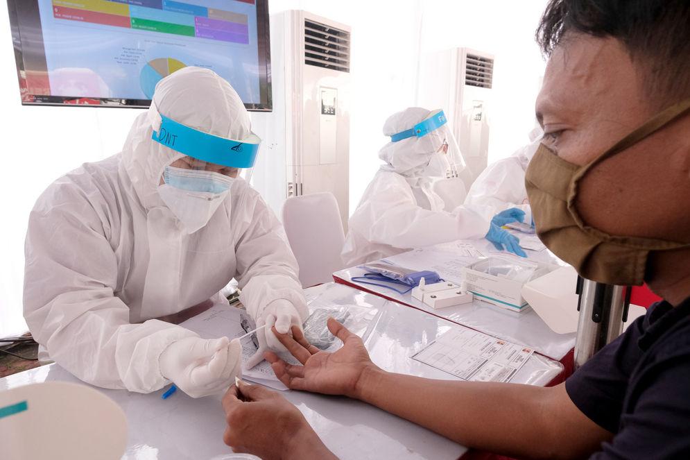 Petugas mengambil sampel darah warga yang mengikuti Mobile Rapid Test (tes bergerak) yang diadakan Relawan Indonesia Bersatu Lawan Covid-19 di Jakarta, Selasa, 21 Juli 2020. Tes cepat secara massal ini diadakan untuk mendeteksi paparan virus corona di masyarakat, terutama di wilayah-wilayah yang menjadi zona merah COVID-19. Foto: Ismail Pohan/TrenAsia\n