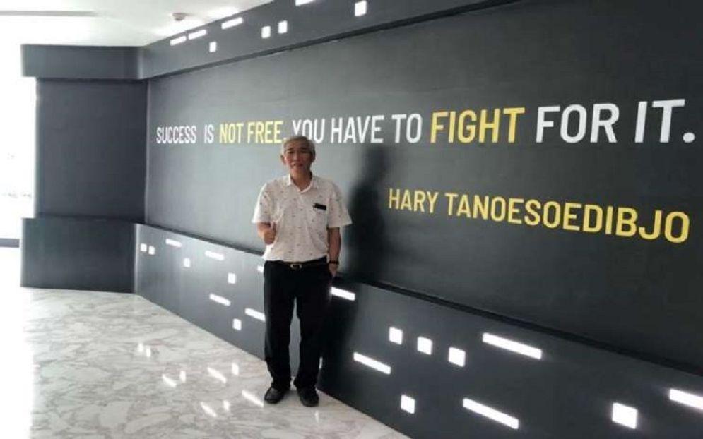 Investor saham Lo Kheng Hong berpose di depan tulisan kata mutiara dari Hary Tanoesoedibjo. / Istimewa\n
