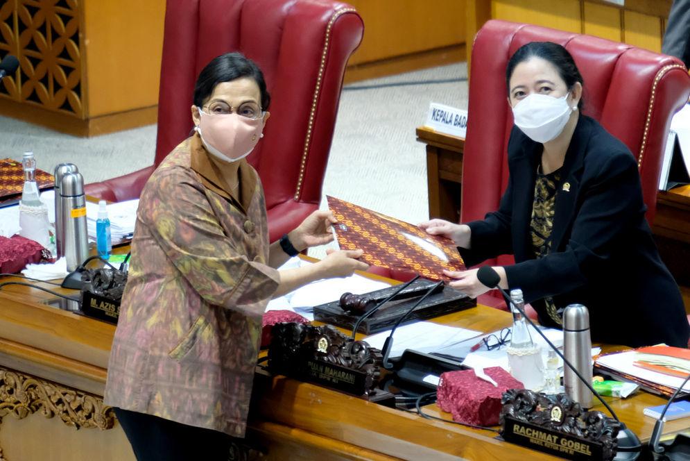 Menteri Keuangan Sri Mulyani (kiri) menyerahkan tanggapan pemerintah atas pengesahan Undang-Undang Anggaran Pendapatan dan Belanja Negara (APBN) tahun 2021 kepada Ketua DPR Puan Maharani (kanan) dalam Rapat Paripurna DPR di Kompleks Parlemen, Senayan, Jakarta, Selasa, 29 September 2020. Rapat Paripurna menyetujui RUU APBN Tahun Anggaran 2021 dan RUU Bea Materai menjadi Undang-Undang serta menetapkan perpanjangan waktu pembahasan RUU Perlindungan Data Pribadi. Foto: Ismail Pohan/TrenAsia\n