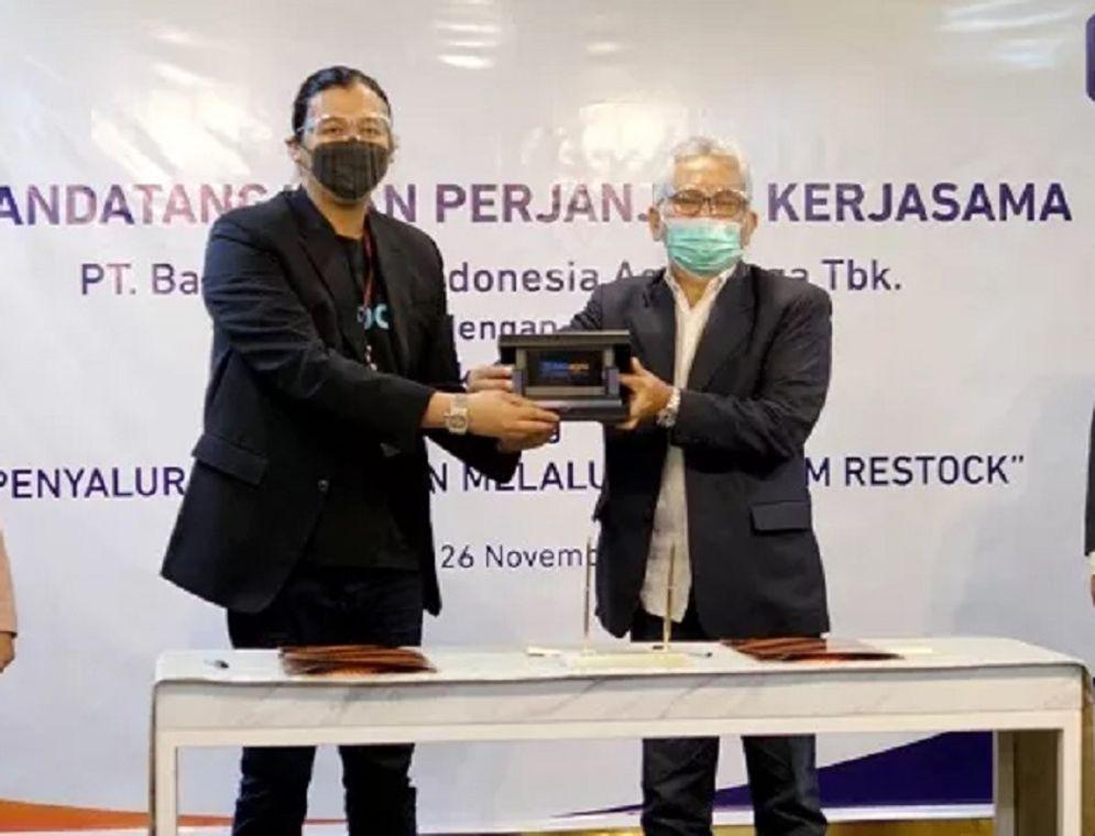 Direktur Utama PT Bank Rakyat Indonesia Agroniaga Tbk (BRI Agro)  Ebeneser Girsang (kanan) bersama Direktur Utama  PT Cerita Teknologi Indonesia (Restock) Muhammad Farid Andika, menandatangani naskah kerja sama, di Jakarta, Kamis, 26 November 2020 / Dok. BRI Agro\n