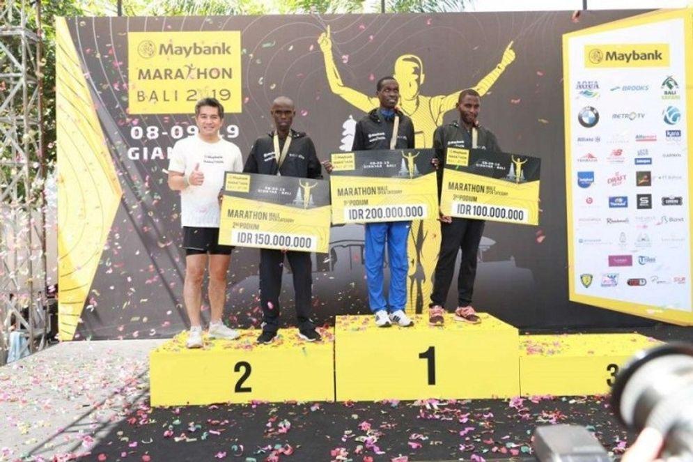 Direktur Utama PT Bank Maybank Indonesia Tbk (BNII) Taswin Zakaria saat memberikan hadiah lomba lari maraton / Dok. Maybank\n