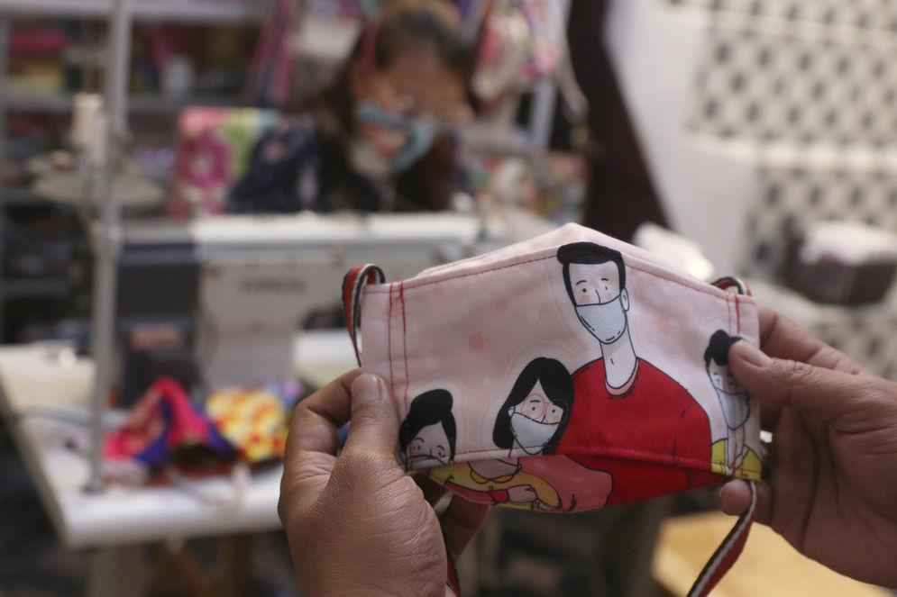 Perajin menyelesaikan produksi masker gambar karakter di industri rumahan Yesya Frita Indonesia, Kota Tangerang, Banten, Jum'at, 27 November 2020. Foto: Ismail Pohan/TrenAsia\n