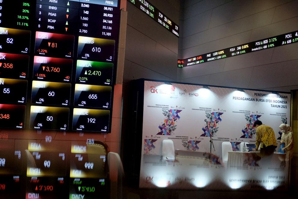 Karyawan beraktivitas dengan latar belakang layar pergerakan Indeks Harga Saham Gabungan (IHSG) di gedung Bursa Efek Indonesia (BEI), Jakarta, Senin, 4 Januari 2021. Foto: Ismail Pohan/TrenAsia\n