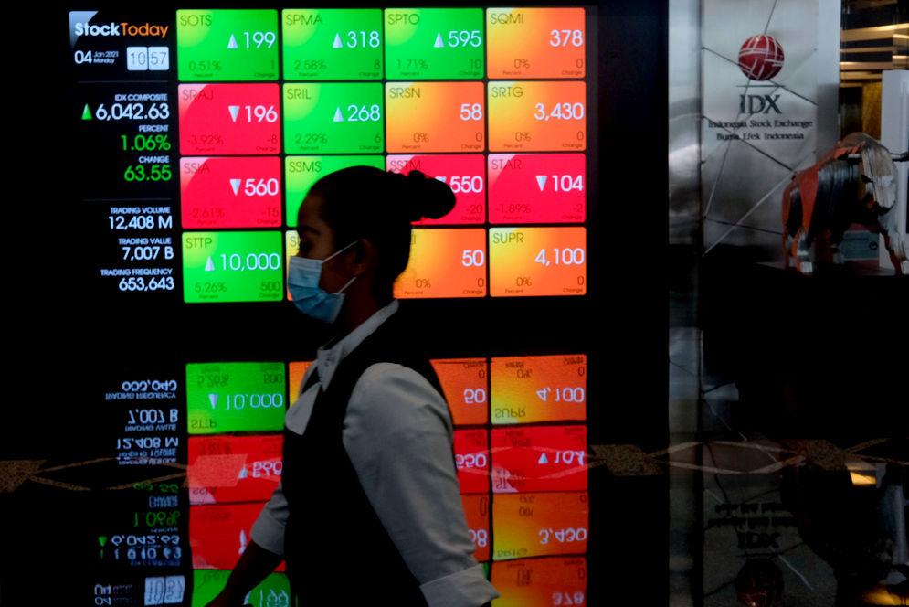 Karyawan melintas dengan latar belakang layar pergerakan Indeks Harga Saham Gabungan (IHSG) di Gedung Bursa Efek Indonesia (BEI), Jakarta, Senin, 4 Januari 2021. Foto: Ismail Pohan/TrenAsia\n