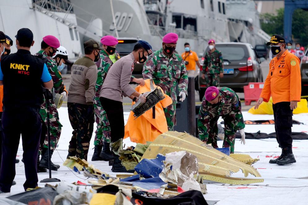Petugas gabungan meletakkan serpihan pesawat di Posko Evakuasi jatuhnya pesawat Sriwijaya Air SJ182 rute Jakarta – Pontianakdi Dermaga JICT, Tanjung Priok, Jakarta Utara, Minggu, 10 Januari 2021. Foto: Ismail Pohan/TrenAsia\n