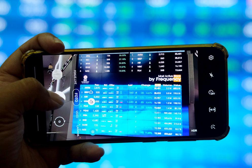 Pewarta mengambil gambar layar pergerakan indeks harga saham gabungan (IHSG) di gedung Bursa Efek Indonesia (BEI), Jakarta, Senin, 15 Februari 2021. Foto: Ismail Pohan/TrenAsia\n