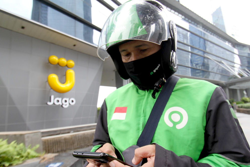 Mitra Driver Gojekmenunggu customer di dekat logo Bank Jago di kawasan Mega Kuningan, Jakarta, Selasa, 16 Februari 2021. Foto: Panji Asmoro/TrenAsia\n