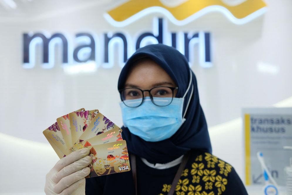 Karyawati menunjukkan kartu debit ATM dengan chip di kantor cabang Bank Mandiri Edu-Branch, Pondok Indah Mall 1, Jakarta, Kamis, 18 Februari 2021. Foto: Ismail Pohan/TrenAsia\n