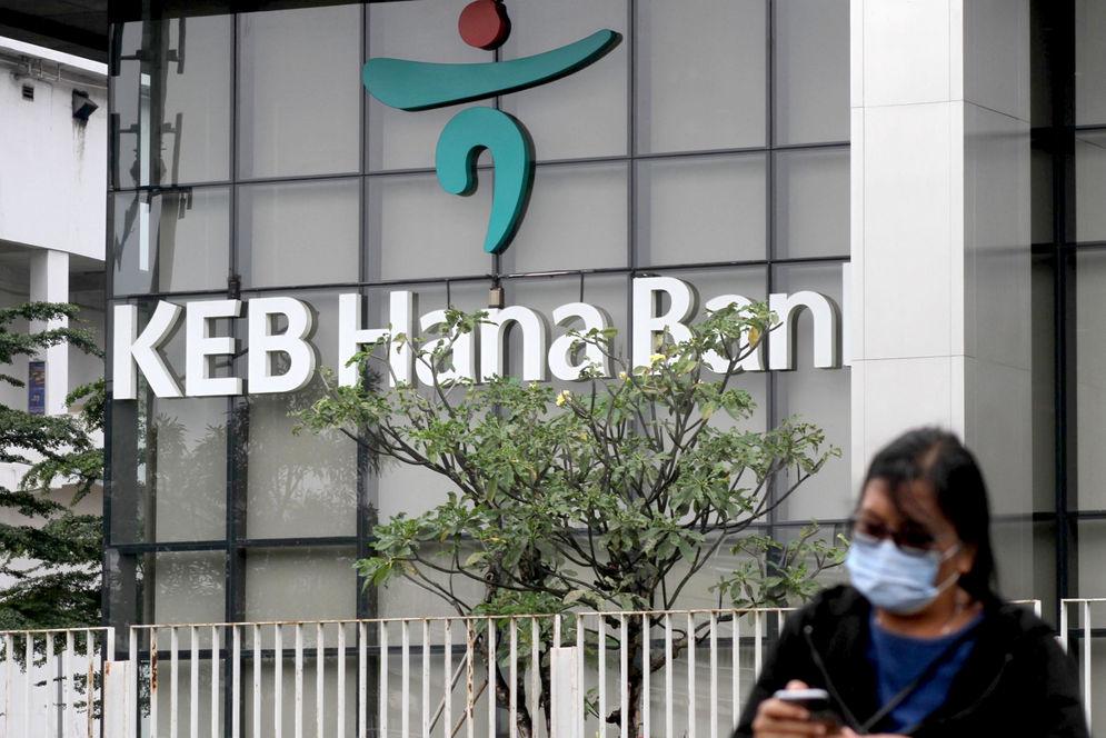 Warga melintas dengan latar belakang logo di gedung KEB Hana Bank, di Jalan Gatot Subroto, Jakarta, Selasa, 16 Februari 2021. Foto: Panji Asmoro/TrenAsia\n