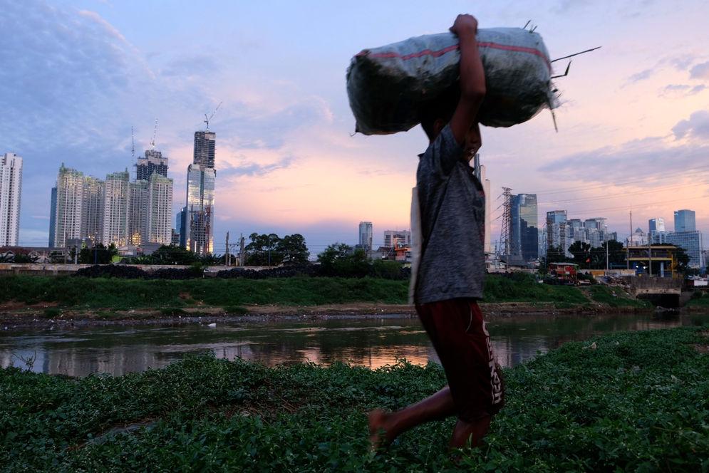 Warga beraktivitas dengan latar belakang gedung bertingkat di kawasan Kebon Melati, Tanah Abang, Jakarta, Rabu, 24 Maret 2021. Foto: Ismail Pohan/TrenAsia\n