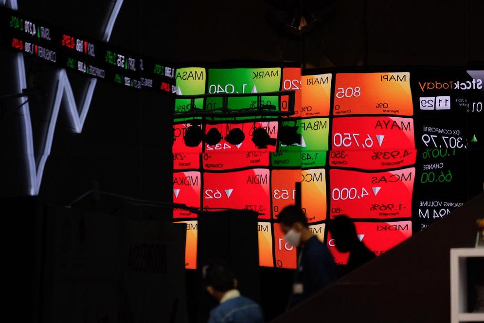 Karyawan melintas dengan latar layar pergerakan indeks harga saham gabungan (IHSG) di Gedung Bursa Efek Indonesia (BEI), Jakarta, Senin, 1 Maret 2021. Foto: Ismail Pohan/TrenAsia\n