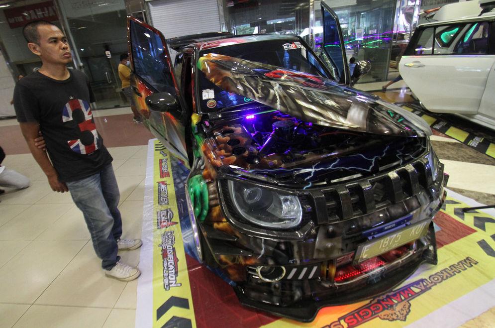 Sejumlah pengunjung mengamati mobil modifikasi yang tengah berlaga dalam Ashar Wheels Auto Contest 2021. Foto: Panji Asmoro/TrenAsia\n