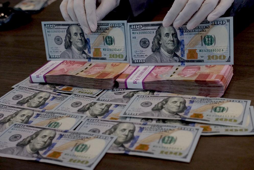 Karyawati menunjukkan mata uang Dolar Amerika dan Rupiah di salah satu teller bank, di Jakarta, Rabu, 3 Maret 2021. Foto: Ismail Pohan/TrenAsia\n