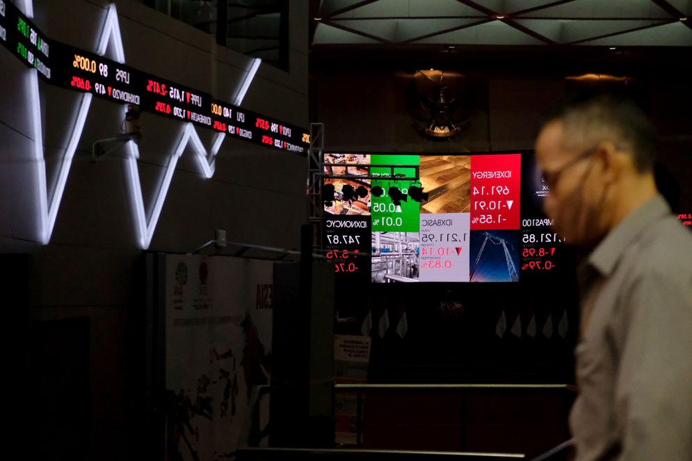 Karyawan beraktivitas dengan latar pergerakan indeks harga saham gabungan (IHSG) di Gedung Bursa Efek Indonesia (BEI), Jakarta, Selasa, 13 April 2021. Foto: Ismail Pohan/TrenAsia\n