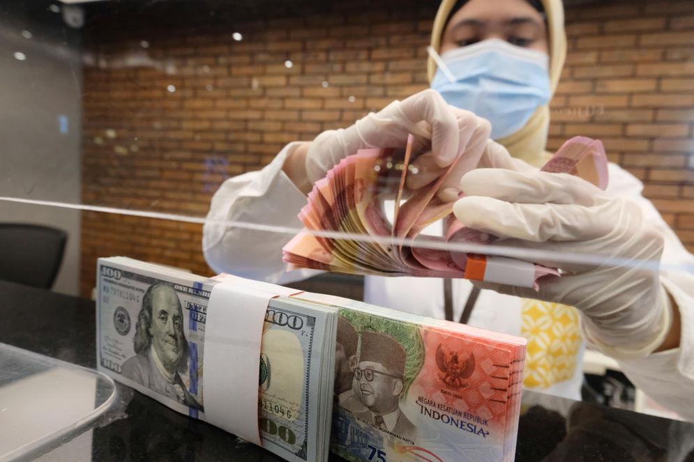 Karyawati menghitung uang di gerai salah satu cabang Bank Mandiri, di Jakarta, Selasa, 6 April 2021. Foto: Ismail Pohan/TrenAsia\n